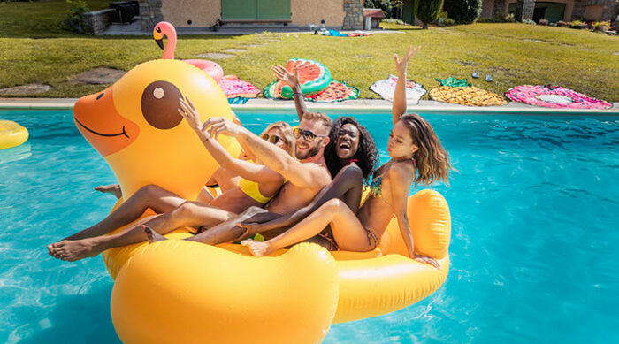 People having fun on a duck shaped pool float in a pool