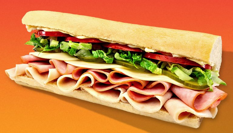 Sub sandwich with meat, cheese, lettuce, and tomatoes